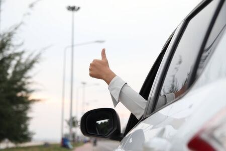 Business hand women with the thumbs up sign from the car Imagens