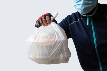 Food service providers wear masks. Sending plastic bags with food to customers who order food online isolated on white background.Ordering food online Was very popular during the period of the Covid-19 virus in Southeast Asia.