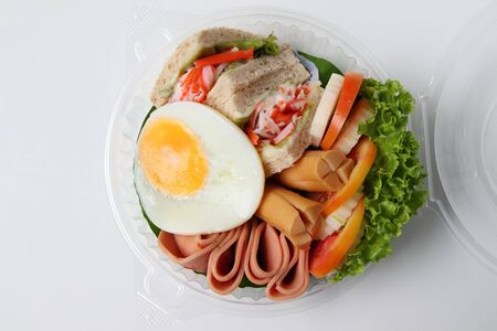 Salad, fried egg, bacon, tomato is packed in a circular plastic box. That was ordered from an food online store.