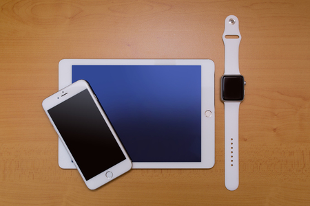 phon: White Smart-phone And Digital tablet And White Smart-watch. On wood desk.