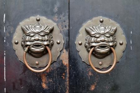 Chinese bronze dragon knocker on wooden doors  photo