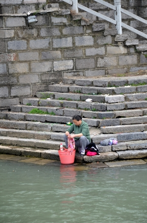 far eastern: Chinese women washes cloth on the river bank Editorial