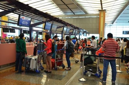 Tourists queue in fronts of ticket counter at Singapore airport