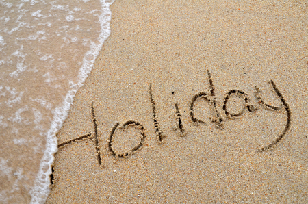 Holiday word written on sandy beach photo