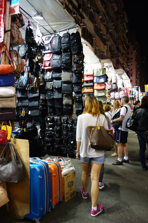 priced: HONG KONG - NOVEMBER 22 :Tourists shop for bargain priced fashion and casual wear in Mong Kong night market on 22 November 2014. The busy night market is famous with many booths setting up to sell local products. Editorial