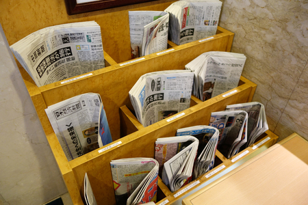 gamut: KYOTO, JAPAN - DEC 9: Various of newspapers located in the rack in Kyoto on December 09, 2014. Japanese newspapers run the gamut from general news-oriented papers to special interest newspapers