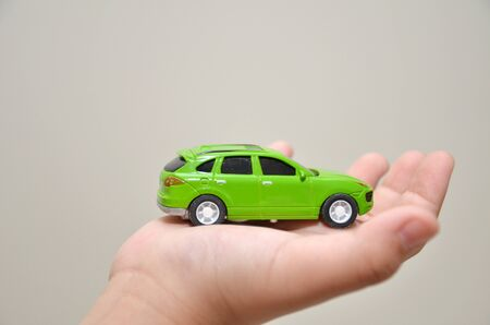 car rent: Green toy car on a right hand with white background