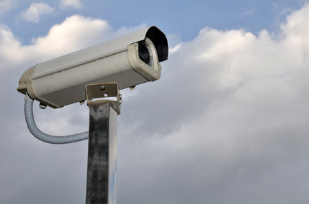Outdoor Security cctv camera under Sun shine and White cloud in blue sky photo