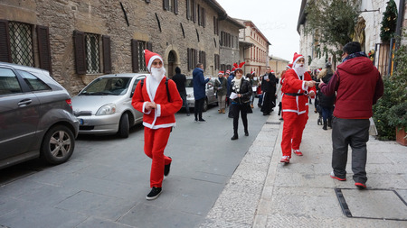needy: MILAN, ITALY - DEC 18, 2014: People dress as Santa play in Milan, Italy. Their purpose is to raise funds for needy and disadvantaged children. Editorial