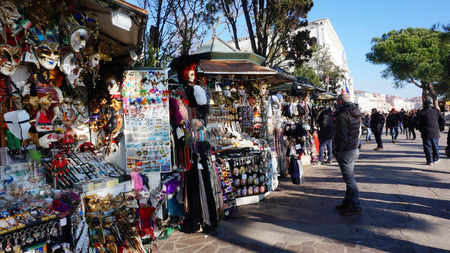the merchant of venice: VENICE, ITALY - NOV 13: Vendors set up a stall on the street to sell colorful mask to tourist in Venice on November 13, 2014. Sales traditional souvenirs like masks, and clothes to tourists visiting Venice is very profitable business.