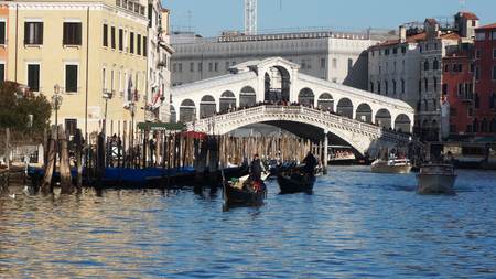 rialto: VENICE, ITALY - JAN 26: Tourists ride on boat under the Rialto bridge in Venice, Italy on January 26, 2015. Rialto Bridge is one of the four bridges spanning the Grand Canal in Venice