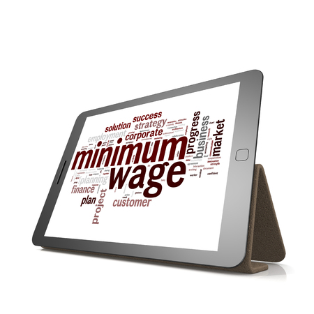 minimum wage: Minimum wage word cloud on tablet image with hi-res rendered artwork that could be used for any graphic design.
