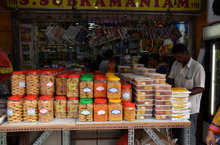 pani: SINGAPORE - NOV 07, 2015: Young men selling local snacks at stall on a pavement in Little India, Singapore.