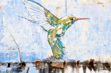 "IPOH, 말레이시아 -2005 년 11 월 23 일 : 유명한 예술가 인 Ernest Zacharevic에 의해 그려진 ""Hummingbird""벽 예술.이 벽화는 먹이를 찾아 나무 위로 떠오르"