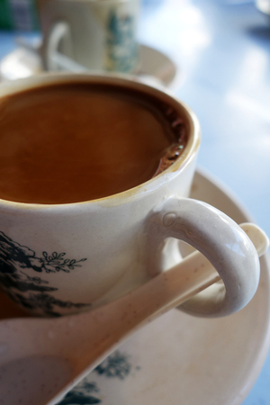 kopitiam: Traditional oriental Chinese coffee in vintage mug and saucer with ambient light