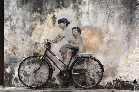 georgetown: PENANG, MALAYSIA- NOV 26 2015: Little Children on a Bicycle street art mural by Lithuanian artist Ernest Zacharevic in Georgetown, Penang, Malaysia.
