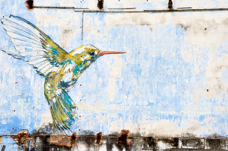 hummingbird: IPOH, MALAYSIA- 23 NOV, 2015: Hummingbird wall art painted by famous artist, Ernest Zacharevic in Ipoh.The mural depicts a hummingbird hovering close by a tree in search of food