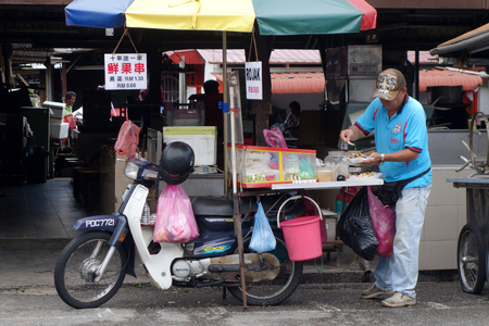 hawker: PENANG, MALAYSIA-26 NOV, 2015: Hawker sells rojak on the road side in Penang, Malaysia. Rojak is a fruit and vegetable salad dish commonly found in Malaysia, Singapore and Indonesia