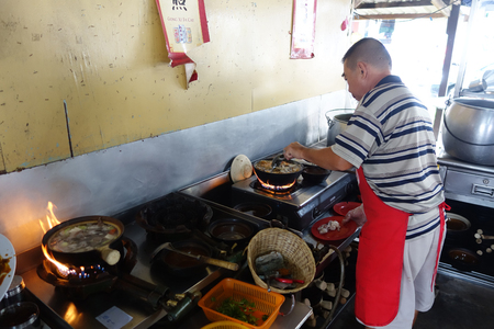 teh: TANJUNG SEPAT, MALAYSIA-27 NOV, 2015: Chef prepares a stew of pork and herbal soup, ba kut teh in Tanjung Sepat, Malaysia. Bak-kut-teh is a meat dish cooked in broth popularly served in Malaysia and Singapore,