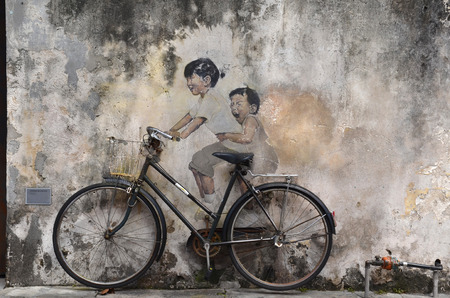 PENANG, MALAYSIA- NOV 26 2015: Little Children on a Bicycle street art mural by Lithuanian artist Ernest Zacharevic in Georgetown, Penang, Malaysia.