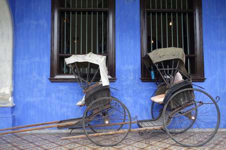 antique tricycle: PENANG, MALAYSIA - NOV 26, 2015:  Old rickshaw tricycle near Fatt Tze Mansion or Blue Mansion, famous oriental historical building in Georgetown, Penang, Malaysia