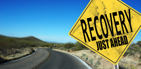 road to recovery: Recovery Just Ahead sign on desert road