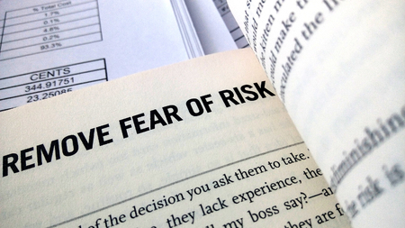 removing the risk: Remove fear of risk word on the book with balance sheet as background Stock Photo