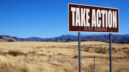 without delay: Take Action Just Ahead brown road sign with blue sky and wilderness Stock Photo