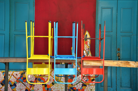 white backing: Colorful chairs on a wooden table in front of old shop, Singapore
