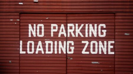 emergency lane: No parking loading zone sign on red metal door
