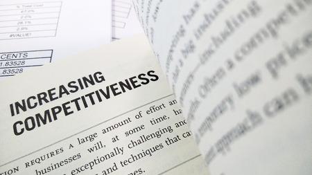 competitividad: El aumento de la competitividad de la palabra en el libro con el balance como fondo Foto de archivo