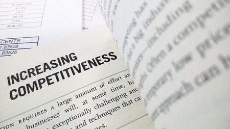 competitividad: Increasing competitiveness word on the book with balance sheet as background