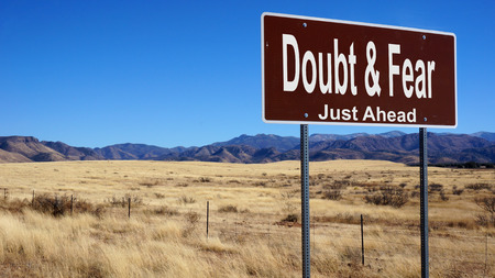 risks ahead: Doubt and Fear road sign with blue sky and wilderness
