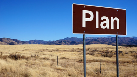 Plan brown road sign with blue sky and wilderness