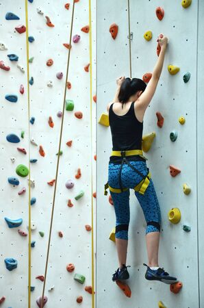 escalate: SINGAPORE - 30 JULY, 2016:  Rave teenage with harness climbing vertical wall, teenage confidence concept. Editorial