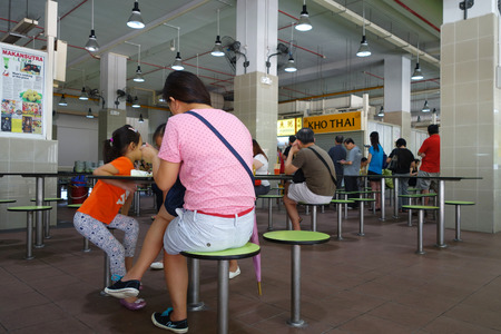hawker: SINGAPORE - 30 JULY, 2016: Amoy street food centre, hawker centre with people having their meals or waiting for food in the morning