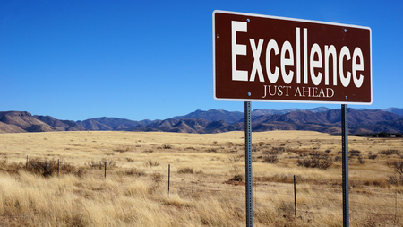 transcendence: Excellence Just Ahead brown road sign with blue sky and wilderness Stock Photo