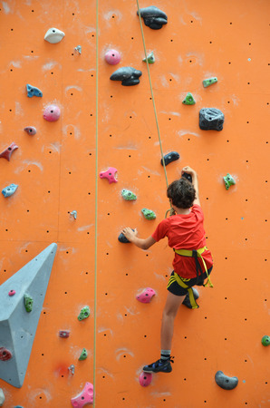 unstoppable: SINGAPORE - 30 JULY, 2016:  Rave teenage with harness climbing vertical wall, teenage confidence concept. Editorial