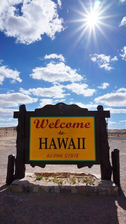 accomplish: Welcome to Hawaii road sign with blue sky