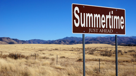 Summertime Just Ahead brown road sign with blue sky and wilderness Stock Photo