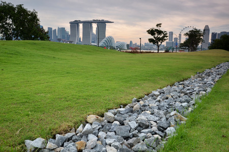 Stock Photo   Stone And Green Grass In The Garden With Singapore Skyline