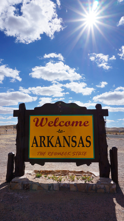 accomplish: Welcome to Arkansas road sign with blue sky