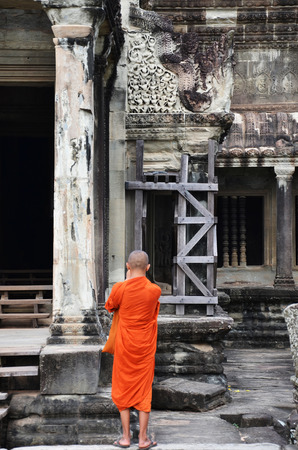 anthropologist: SIEM REAP, CAMBODIA - OCT 20, 2016: Monk enters an ancient temple at Angkor Wat, Siem Reap in Cambodia.