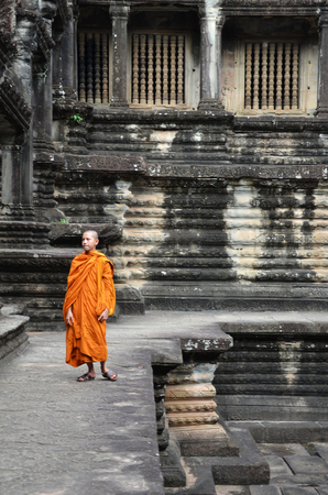 SIEM REAP, CAMBODIA - OCT 20, 2016: Monk enters an ancient temple at Angkor Wat, Siem Reap in Cambodia.