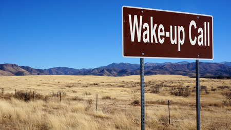 portent: Wake up Call road sign with blue sky and wilderness