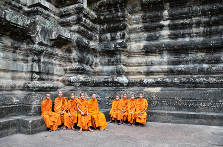 SIEM REAP, CAMBODIA - OCT 20, 2016: Buddhist monk in reddish yellow robes in one of the famous temples of Angkor Wat, Siem Reap, Cambodia Editorial