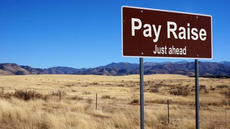 pay raise: Pay Raise road sign with blue sky and wilderness Stock Photo