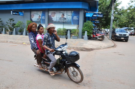 prevalent: SIEM REAP, CAMBODIA - OCT 20, 2016: Family of three on a motor bike going through the streets of  Siem Reap, Cambodia