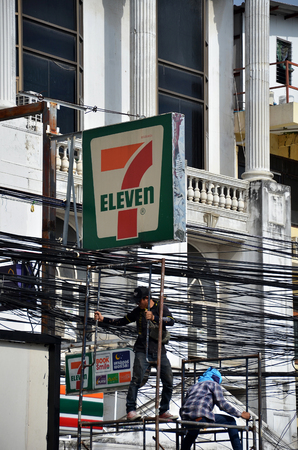 essentially: PATTAYA, THAILAND - 19 NOV, 2016: Electrician lineman repairman worker at climbing work on electric post power pole under 7-11 sign Editorial