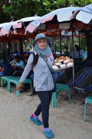 merchant: PATTAYA, THAILAND - 22 NOV, 2016: Local merchant selling souvenirs to tourists at Pattaya beach